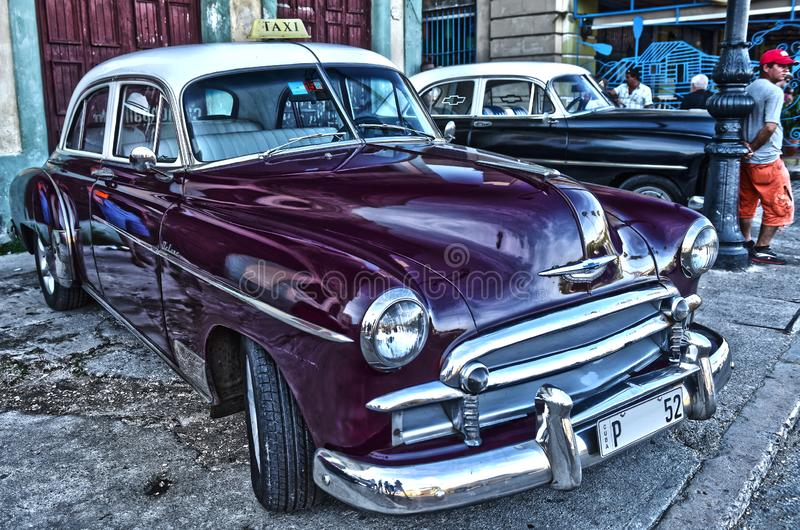 Standing on the Corner of Classics. The nastalgic American classic`s are a very popular mode of transportation in Cuba. Here are some 1950 Chevy taxi`s on a royalty free stock photos