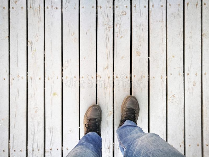 Human feet and legs seen from above. Standing on dirty white wooden pathway; wearing dusty sport shoes and blue jeans in backpacker style - Copy-space for add stock photography