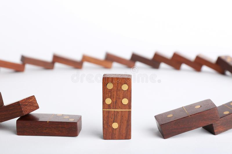 Standing domino piece among fallen ones on white royalty free stock photo