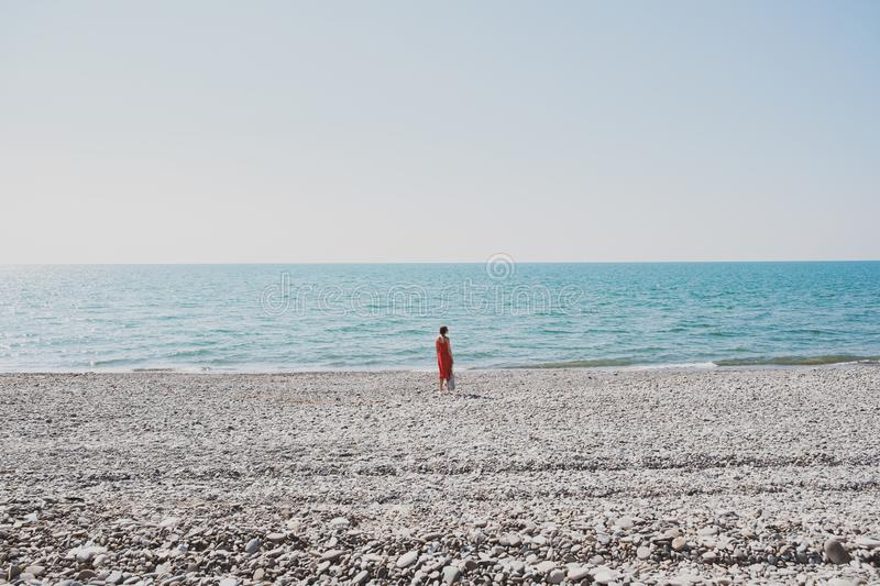 Standing on an empty pebble shore by the sea, concept of summer vacation and rest stock image