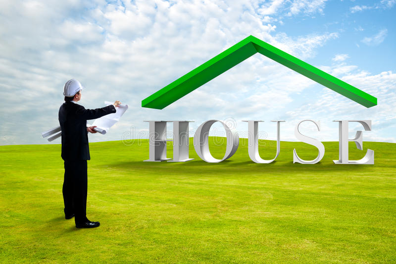 Standing engineer looking house 3D. On green grass royalty free stock images