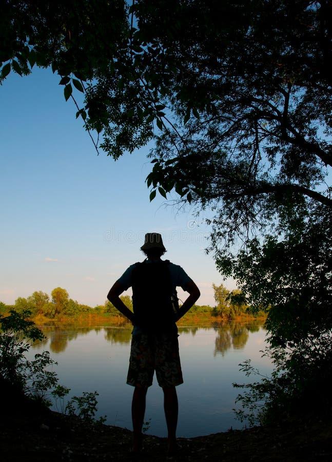 standing för silhouette för manflodkust fotografering för bildbyråer