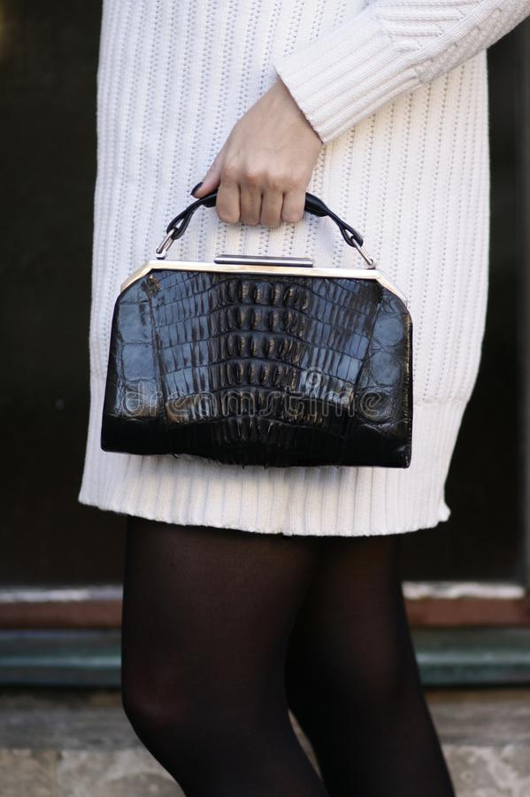 Black art deco crocodile purse and white sweater fashion detail royalty free stock image