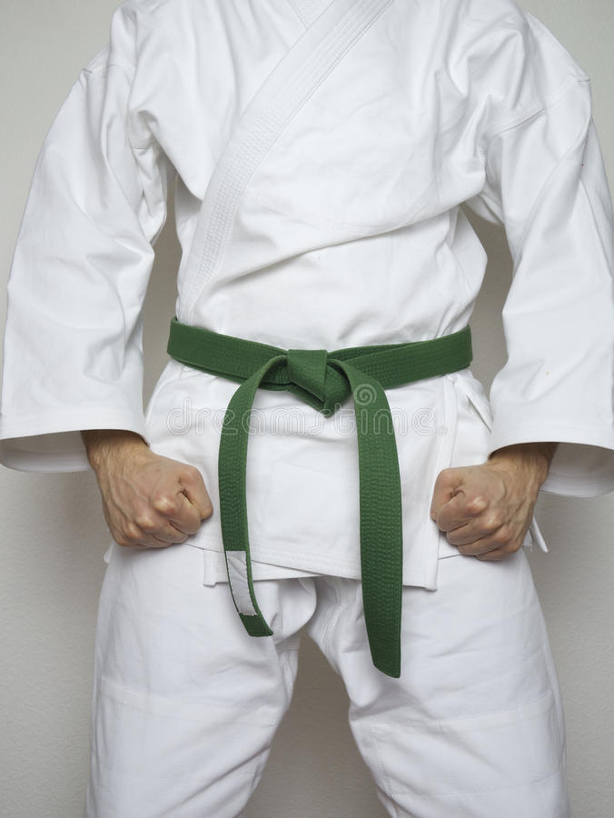 Standing fighter green belt martial arts white suit. Standing fighter with green belt martial arts in white suit royalty free stock photography