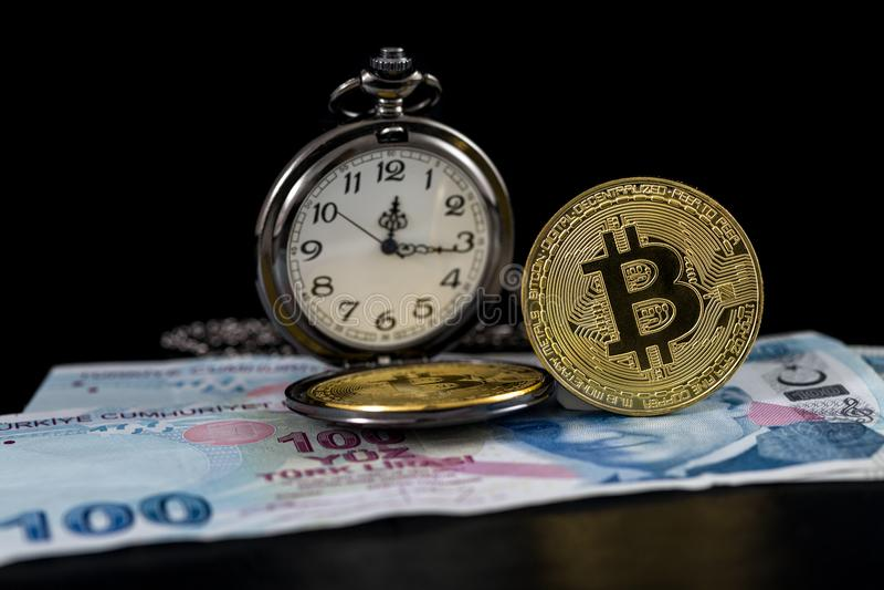 Standing golden bitcoin and pocket watch on turkish lira stock photo