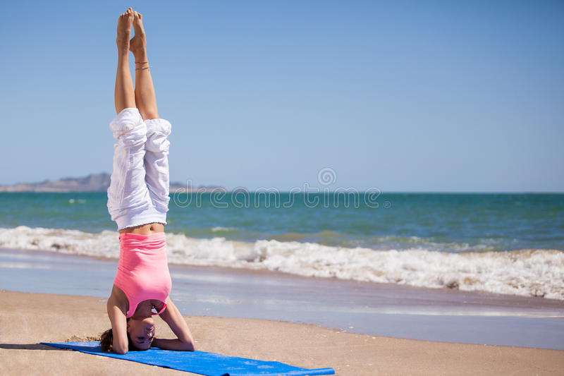 Standing on her head at the beach. Cute Hispanic woman doing some yoga and standing on her head at the beach stock photos