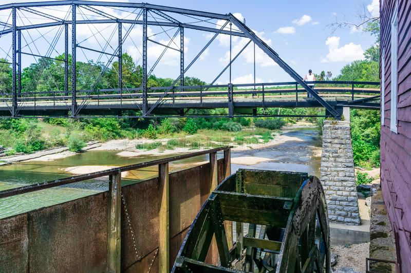 Standing on the historic War Eagle Bridge in Rogers, Arkansas one can see the working water wheel powered by the War Eagle River stock image