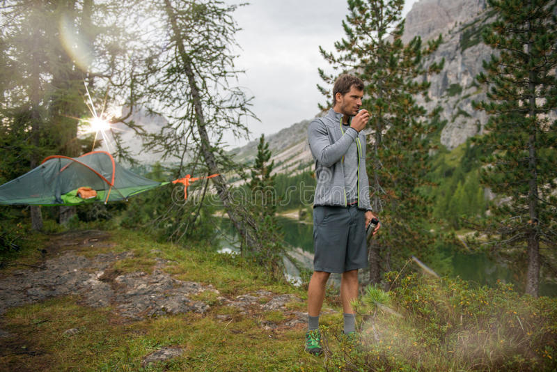 Standing man drinking hot beverage near hanging tent camping at lake with sun light.Group of friends people summer. Adventure journey in mountain nature royalty free stock photos