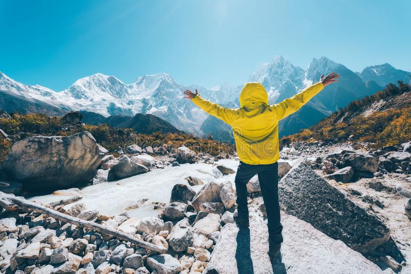 Man with raised up arms near the river against mountains stock photography
