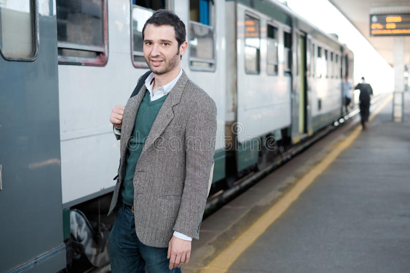 Standing man waiting for the train in a train station platform stock images