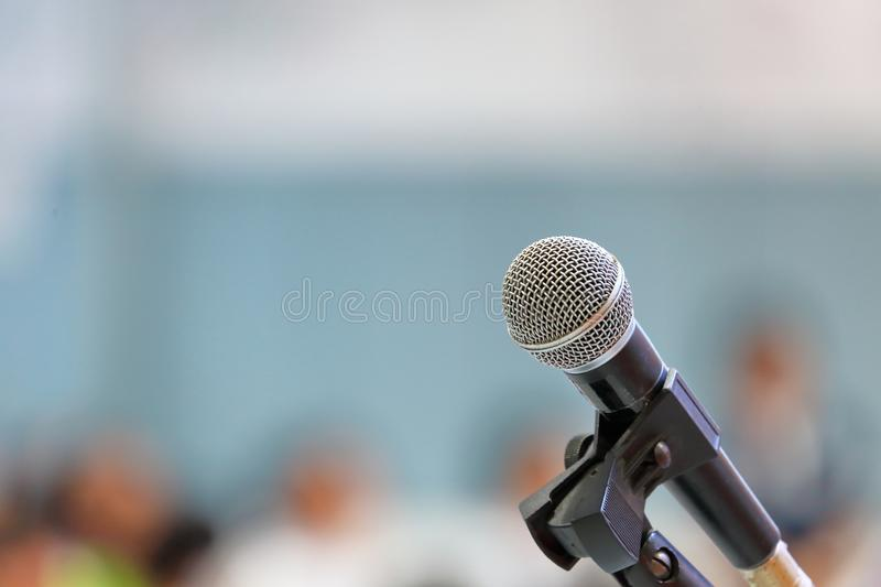 Standing microphone for speaker`s speech in the seminar room with audience in the background. Microphone for speaker`s speech in the seminar room with audience royalty free stock images