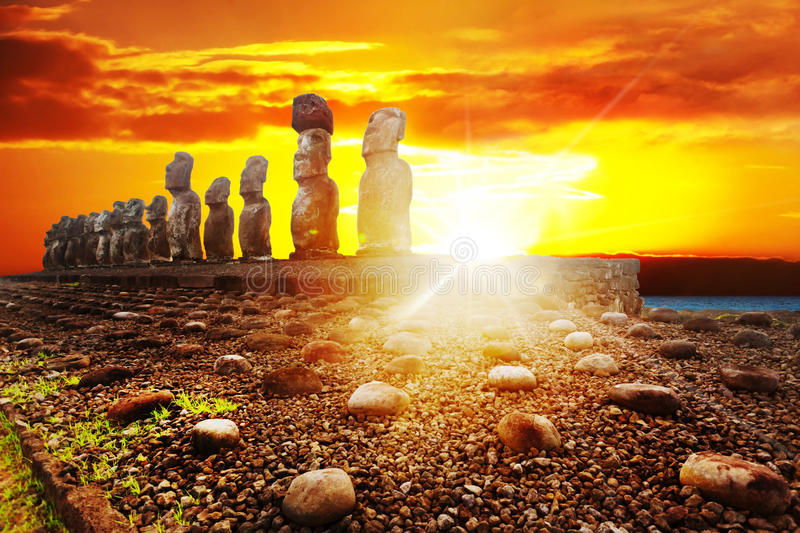 Standing moais in Easter Island in dramatic orange sunset. Fifteen standing moais in Easter Island in dramatic orange sunset royalty free stock photo