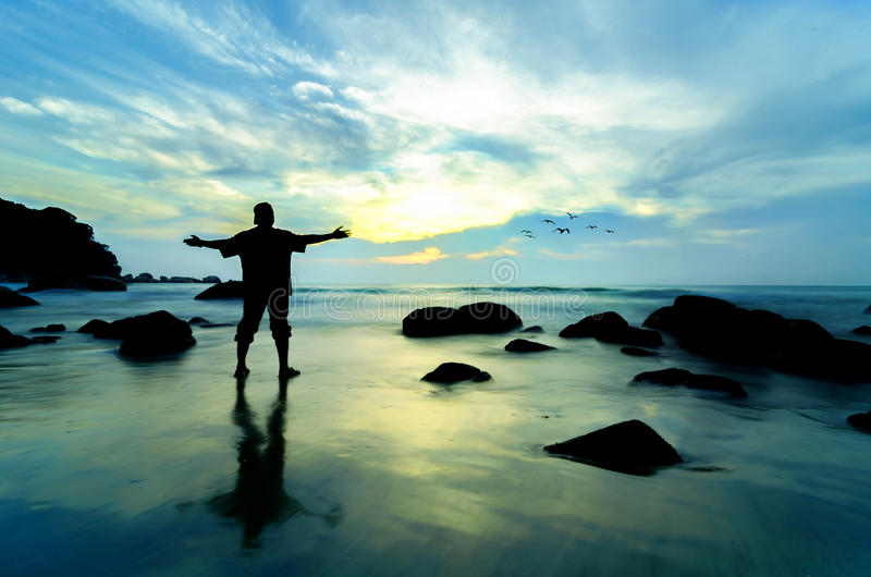 Standing near the beach looking at sun rising. Man standing near the beach looking at sun rising royalty free stock image