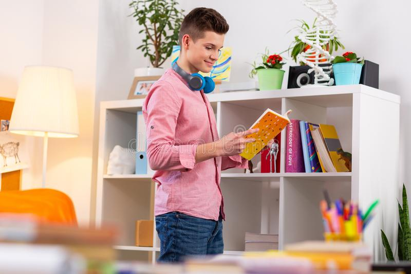 Student standing near bookcase and choosing the book to read royalty free stock photography
