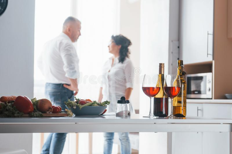 Standing near the window. Senior man and his wife in white shirt have romantic dinner on the kitchen royalty free stock image