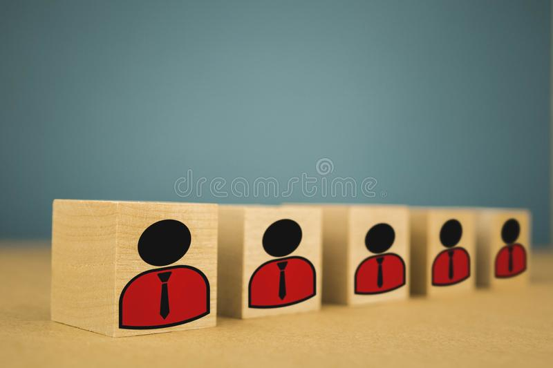 Standing in a row wooden cubes on a blue background, denoting a standing bosses in a row. Hand business icon man recruit talent concept resource human skill royalty free stock images