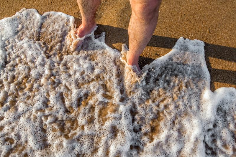 Standing on the shoreline while foaming sea water is surging towards brown sand at sunset. Black Sea.  royalty free stock images