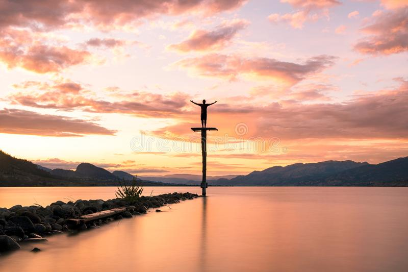 Standing Silhouette at Sunset over Lake Okanagan in British Columbia. Photographer Aaron Northcott poses for a silhouette photograph atop a large platform as the royalty free stock photography