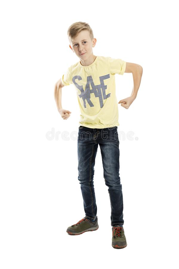 Standing teenager boy in jeans and a yellow T-shirt shows muscles. Full height. Isolated over white background. Standing teenager boy in jeans and a yellow T royalty free stock photography