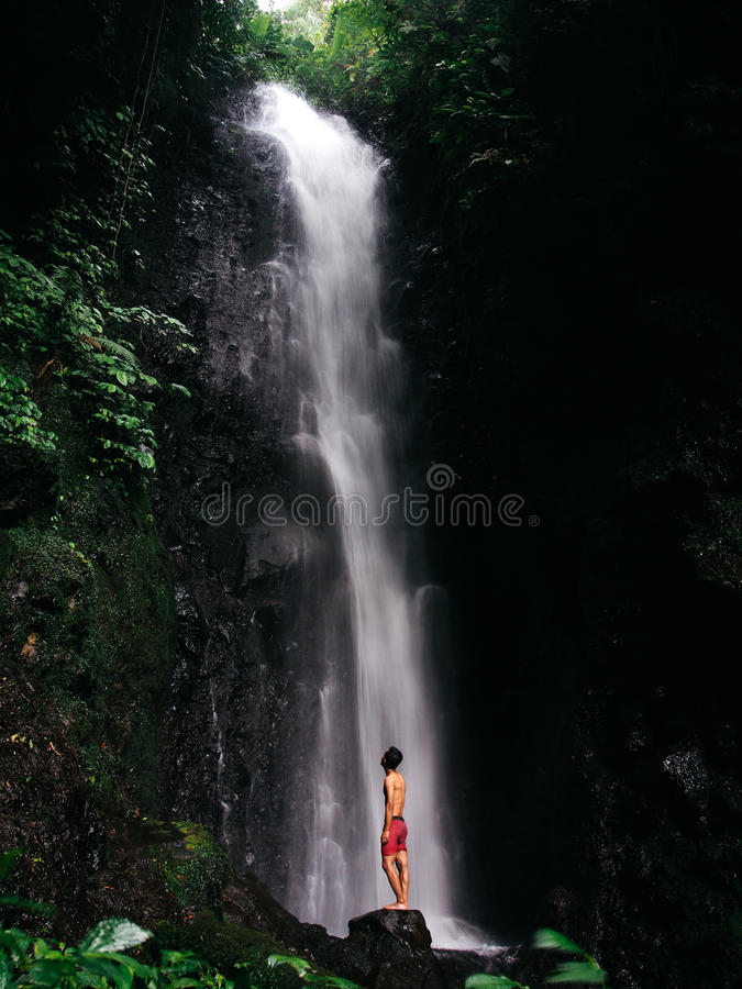 Standing Under Waterfall stock photo