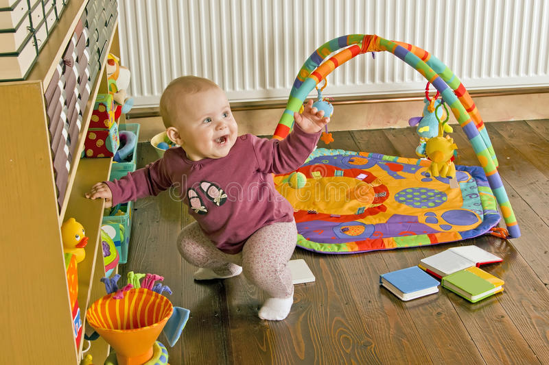 Standing up baby. Baby standing on her feet holding on shelf royalty free stock image