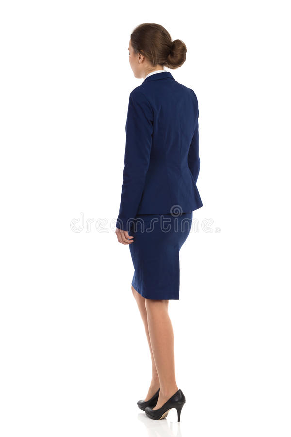 Standing Woman In Blue Formalwear Side Rear View. Young woman in blue suit, skirt and black high heels standing. Rear side view. Full length studio shot isolated stock photo