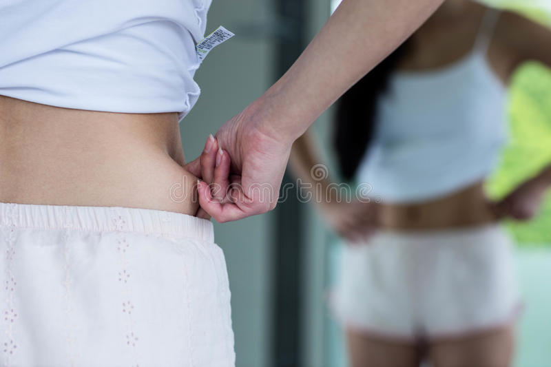 Standing woman pinching her hip. In bathroom royalty free stock images