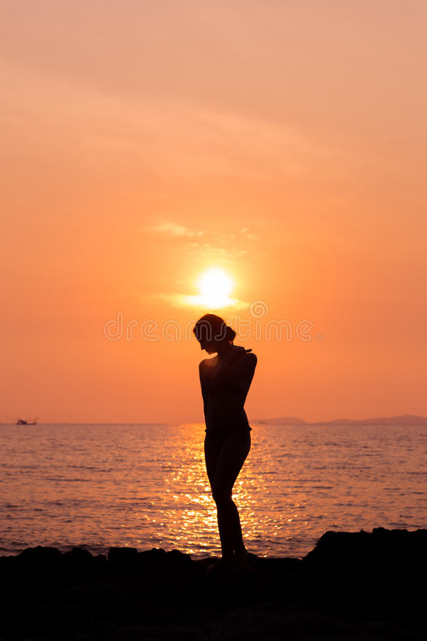 Standing woman silhouette on sea background royalty free stock image