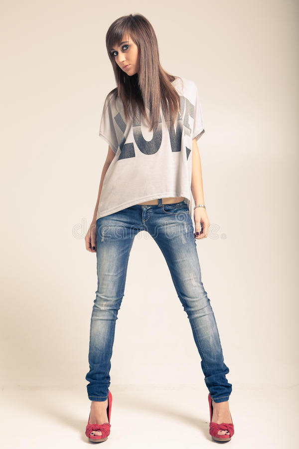 Standing young woman wearing jeans royalty free stock photo