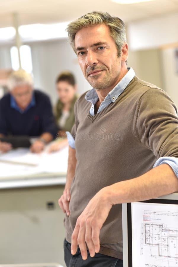 Standintg d'homme d'affaires au bureau des architectes images libres de droits
