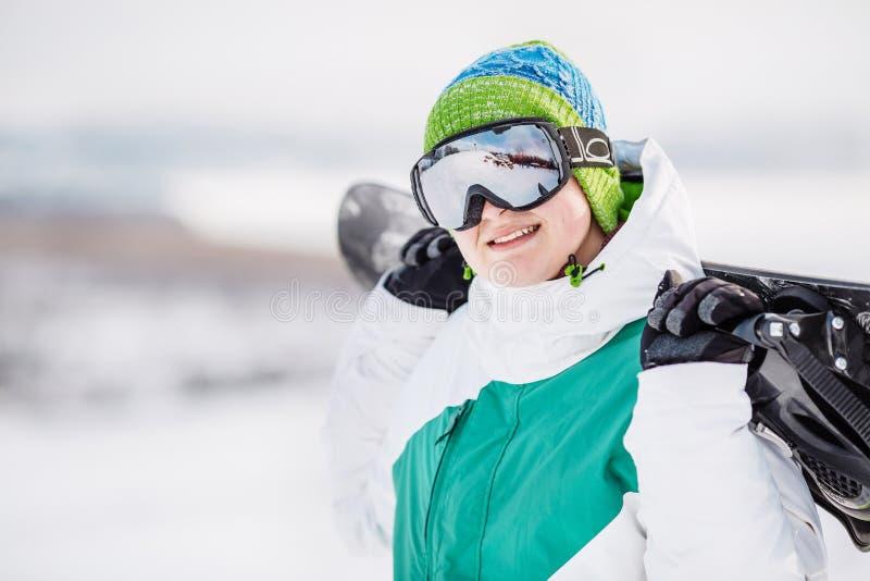 Standng de jeune homme sur la neige avec le surf des neiges photographie stock libre de droits