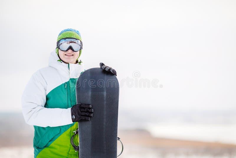 Standng för ung man på snön med snowboarden royaltyfria bilder
