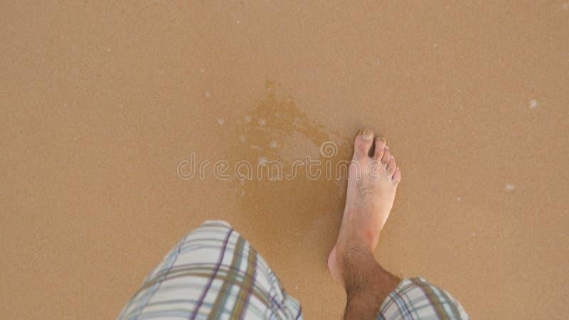 Standpunt die van de jonge mens bij het gouden zand op zee strand stappen Mannelijke benen die dichtbij oceaan lopen Naakte voet  royalty-vrije stock foto