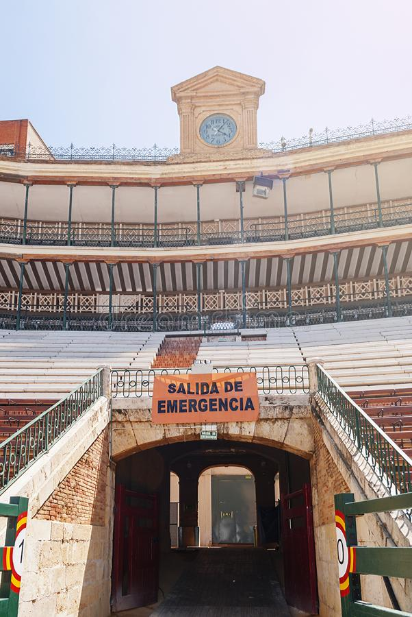 Stands with an emergency exit and the ancient clock of a Spanish arena. View of the stands with an emergency exit and the ancient clock of a Spanish arena stock photography