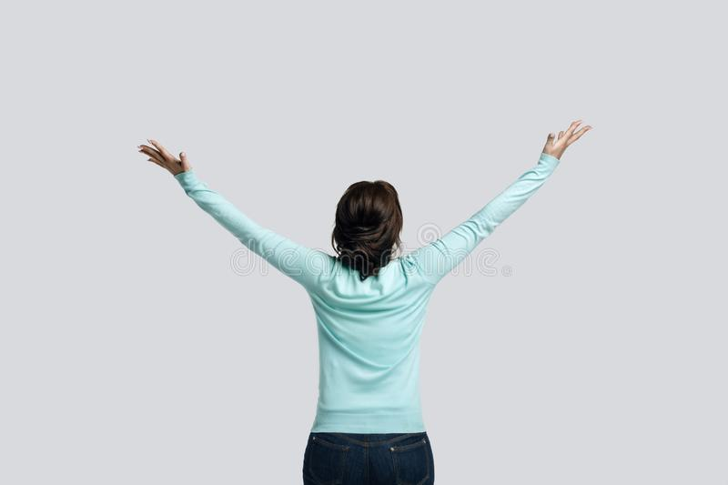 She stands with her back holding her arms up,. A brunette woman in a mint-colored jumper stands against the background of a delicate, she stands with her back stock photography