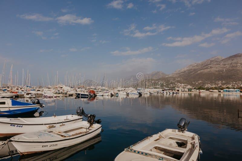 Stange, Montenegro - 31. November 2018 Fischerboote auf dem Hintergrund von Bergen und von Yachten auf der adriatischen Küste - B stockfotografie