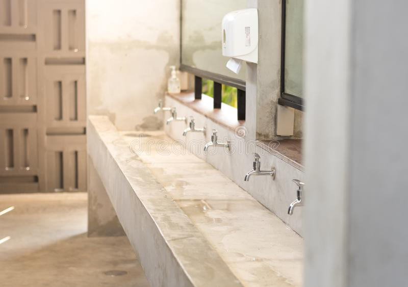 Stanless steel taps above concrete sink in a shared toilet. stock photos