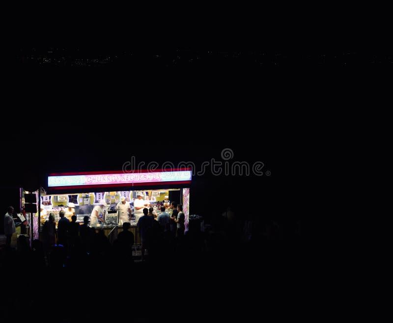 Stannar lång exponering för natten med det ljusa neontecknet av en snabbmat sälja churros och andra sötsaker på gatan arkivfoto