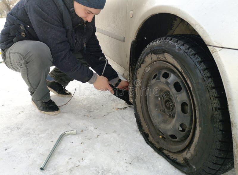 Stansat och plant gummihjul på vägen Utbytning av hjulet med en stålar vid chauffören royaltyfri foto