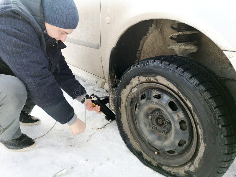 Stansat och plant gummihjul på vägen Utbytning av hjulet med en stålar vid chauffören royaltyfri fotografi