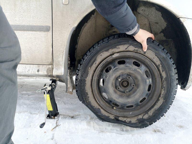 Stansat och plant gummihjul på vägen Utbytning av hjulet med en stålar vid chauffören arkivfoton