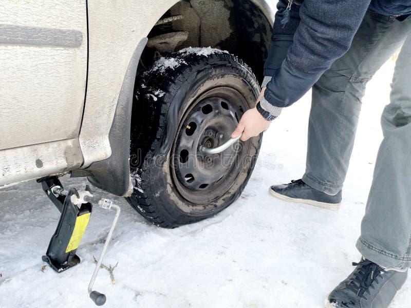 Stansat och plant gummihjul på vägen Utbytning av hjulet med en stålar vid chauffören arkivbild