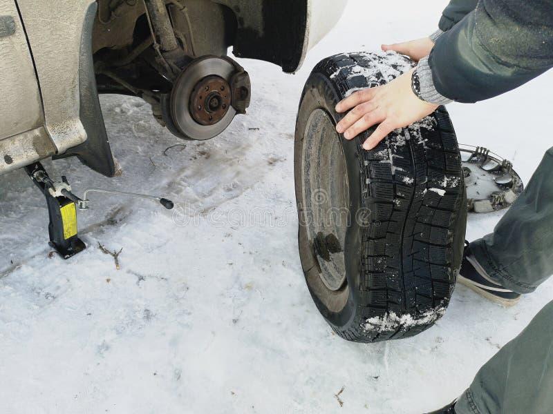 Stansat och plant gummihjul på vägen Utbytning av hjulet med en stålar vid chauffören arkivfoto