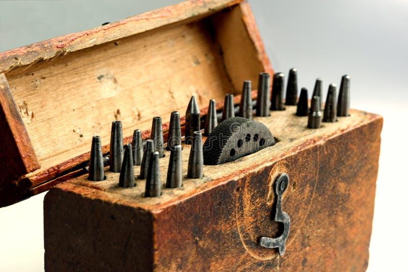 Stansmaskiner för ett hörn för tappningcirkulärrunda ställde in med ett städ med öppningar i en träask arkivfoto