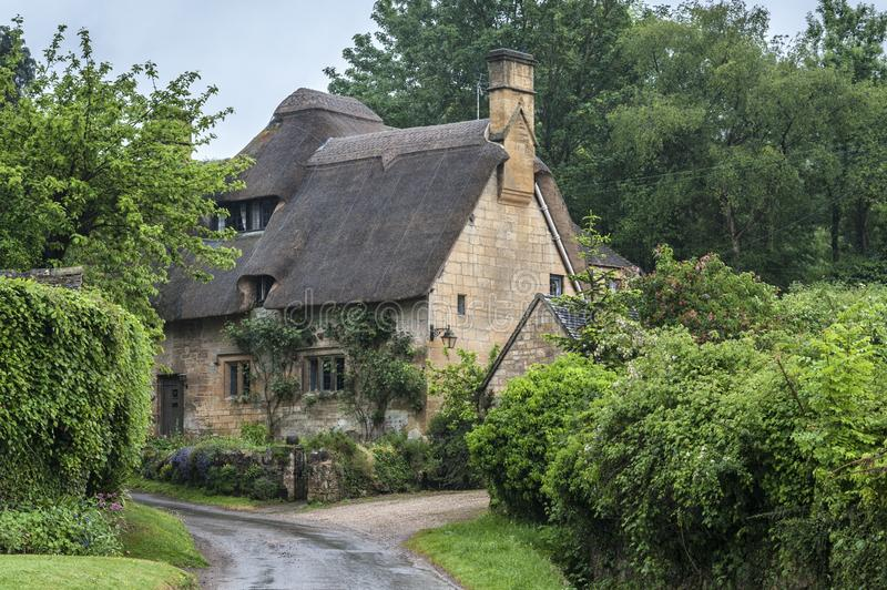 Thatched cottage in the village of Stanton, Cotswolds district of Gloucestershire.  It`s built almost completely of Cotswold stone royalty free stock image