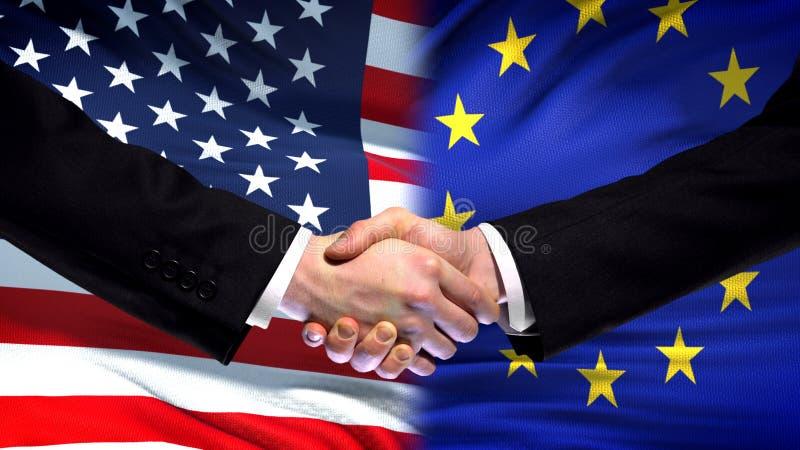 Stany Zjednoczone i UE uścisk dłoni, międzynarodowa przyjaźń, chorągwiany tło zdjęcia royalty free