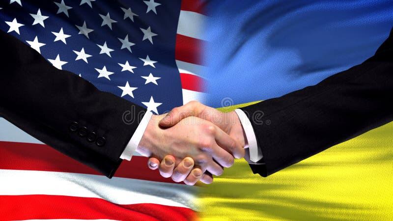 Stany Zjednoczone i Ukraina uścisk dłoni, międzynarodowa przyjaźń, chorągwiany tło obrazy royalty free