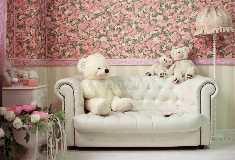 Stanza accogliente bianca e rosa con gli orsacchiotti sofà e lampada bianchi dei fiori fotografia stock libera da diritti