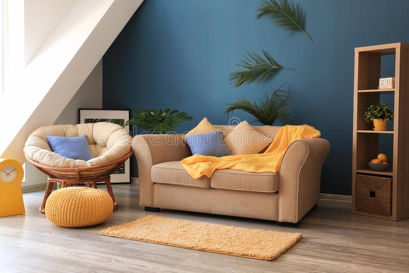 Stanza alla moda interna con il sofà e le foglie tropicali sulla parete immagini stock