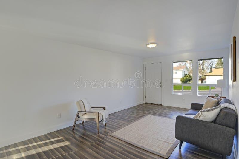 Stanza bianca dell'entrata con il sofà trapuntato comodo immagini stock libere da diritti
